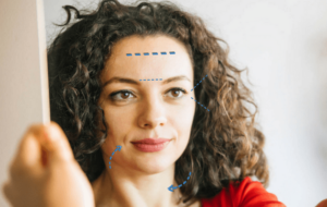 Beautiful Woman Looking in Mirror with Laser Treatment Areas Marked