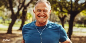 older mean on gym shirt and listening to his headphones