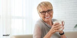 Blond older female drinking coffee